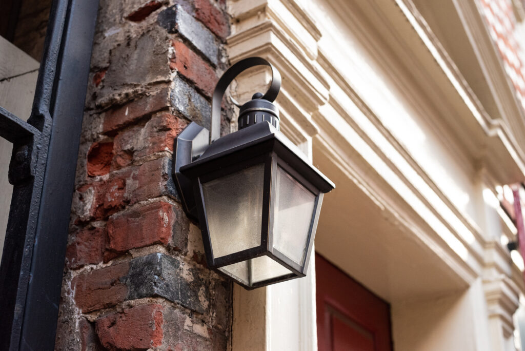 A porch light during the day in front of a red brick wall.
