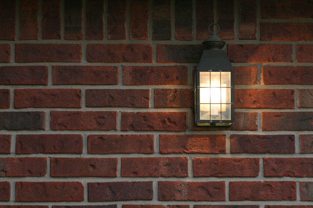 A porch light in front of a red brick wall.